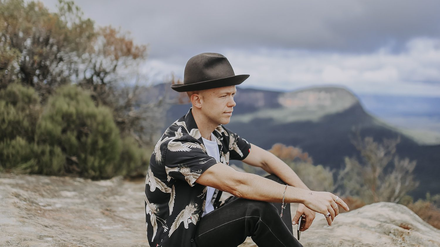 Justin Hunter musician sitting on rock in the Blue Mountains looking at the valley